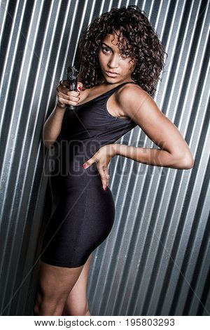 Beautiful black woman pointing gun