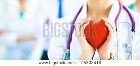 Female doctor with stethoscope holding heart