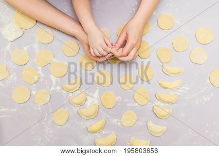 From above mother and child hand's make ravioli. Cooking together with children. Child learning how to make dumplings.