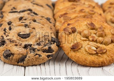 Biscuits with chocolate and peanut on old wooden table. Selective focus.