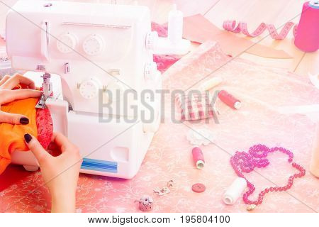 Close up of girls hands sewing dress with the help of sewing machine. Dressmaker's workplace: sewing machine spools necklace measuring tape needles