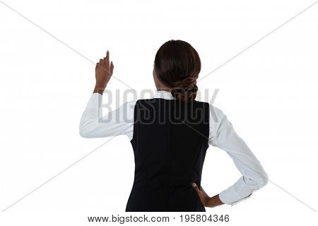 Rear view of businesswoman with hand on hip using invisible interface against white background