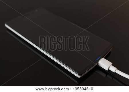 Black Smart Phone Charging with Cable on the Black Table