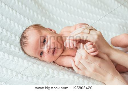 Portrait of newborn baby girl princess with crown on soft white blanket. Mother's hands holding baby.