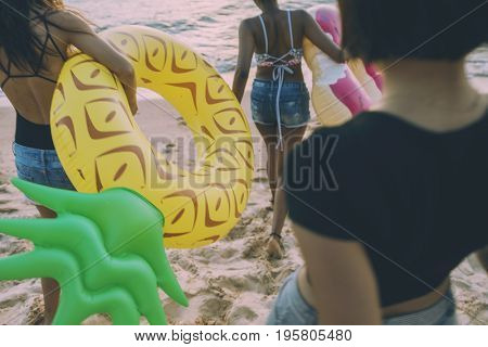 Group of diverse women walking at the beach with inflatable tubes