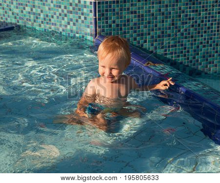 Picture of a small laughing child in a swimming pool