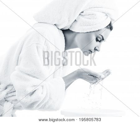 Young woman washing face with clean water in white bathrobe and towel. Morning hygiene concept.