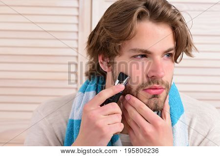 Man Holds Razor And Starts Shaving His Beard