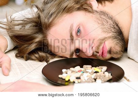 Pills On Plate Near Motionless Guy With Beard