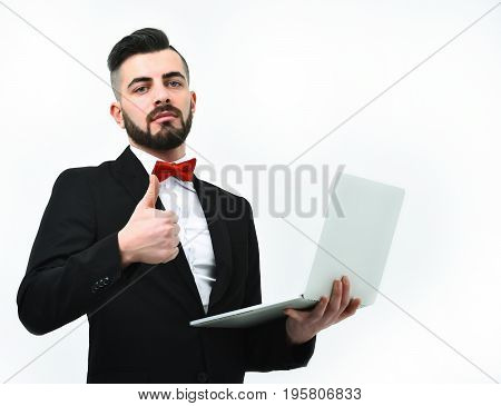 Businessman or CEO with beard fancy suit and red tie shows thumbs up and holds high tech computer isolated on white background. Concept of good management and business
