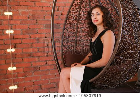 beautiful girl in black evening dress sitting in the luxury nest-armchair. Supermodel, indoor