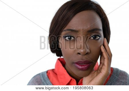 Portrait of surprised woman with hand on chin against white background