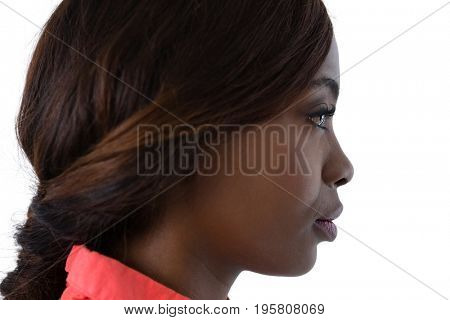 Side view of woman with brown hair looking away against white background