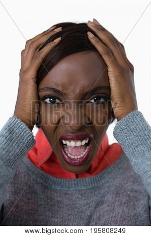 Portrait of young woman shouting with head in hand against white background