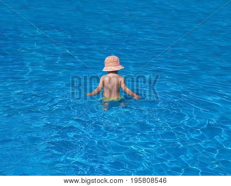 small baby in a hat bathes in a pool