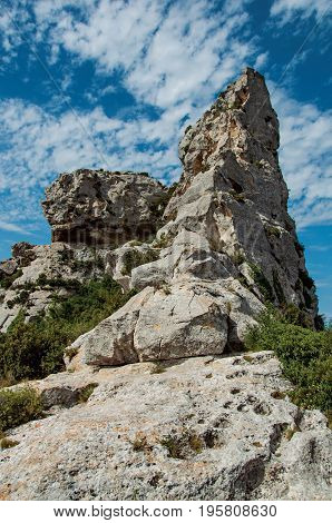 Cliff with blue cloudy sky, near Baux-de-Provence. Located in the Bouches-du-Rhône department, Provence-Alpes-Côte d'Azur region, in southeastern France