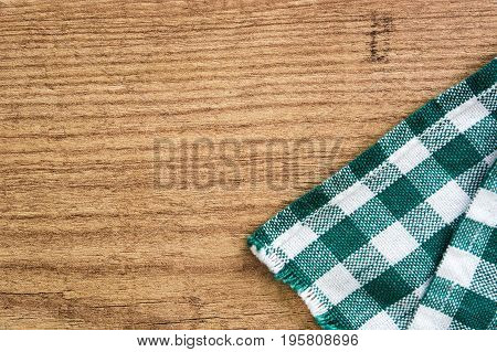 Wooden and green checkered tablecloth. Top view copyspace.
