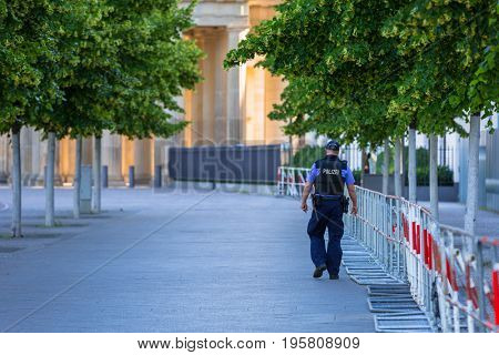 BERLIN, GERMANY - JUNE 15, 2017: Policeman on guard in the city center of Berlin, Germany. Berlin is the capital and the largest city of Germany with a population of approximately 3.7 million people.