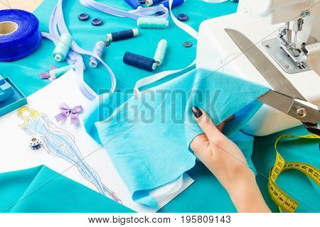 Close up of girl's hands cutting blue fabric with the help of scissors.
