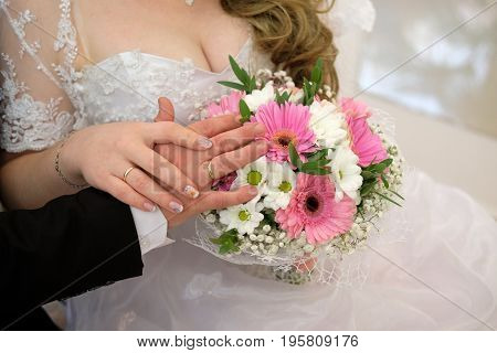 The bride and groom show wedding bands and wedding bouquet