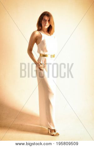 Young woman in a full-length mirror in a white dress on a white background.