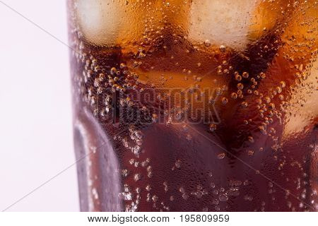 Bubbles and fizz. A cool glass of cola drink with ice