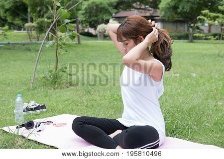 Young Asian Woman Ties Her Hair In A Ponytail While Sitting In Public Park
