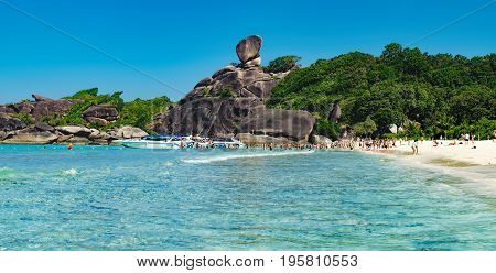 Phang Nga, Thailand - January 4, 2016: Koh Similan No.8 Island with Sailing Boat Rock in Similan National park, Phang Nga, Thailand. Tourists arrive by boat and to walk through the waves to the beach