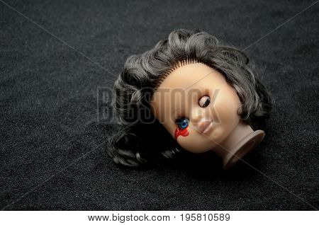 Doll head on black Sand with blood