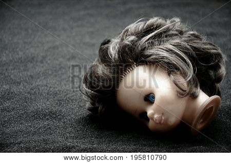 Doll head on black Sand dark scene