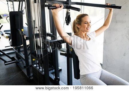 Young beautiful woman working in gym on shoulder press machine