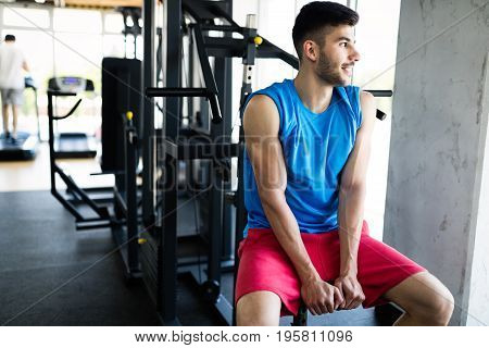Young attractive man at gym having break from workout
