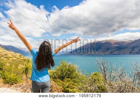 New Zealand travel happy tourist woman with arms up at Wanaka lake nature landscape outdoors. Wanderlust adventure young girl with peace hand sign.