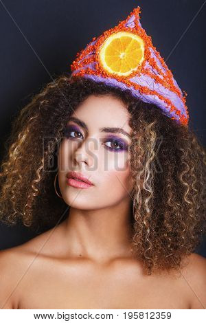 Young black woman with afro hairstyle and make up . Ethnic woman with flower and fruit diadem. Studio shot.