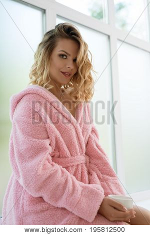 Beautiful blonde wearing nice pink soft bathrobe sitting on window sill studio portrait