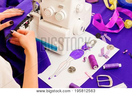 Close up of girls hands sewing dress with the help of sewing machine. Dressmaker's workplace: buckle ribbons buttons spools sewing machine fabric and sketch