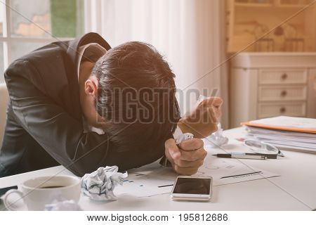 A stressed out business man holds his head in despair as he fears that he will have to file for bankruptcy or go into liquidation poster