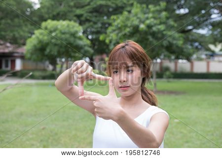 Asian Girl Making Frame Capture With Hands. Young Woman Taking Picture With Imaginary Camera In Publ