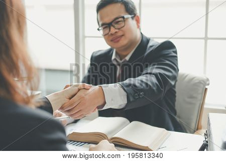 Business man and business woman shaking hands teamwork concept