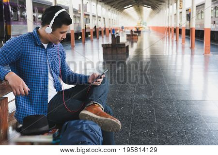 Asian Man With Backpack Sitting On Platform At Train Station. Backpacker Or Traveler With Headphone