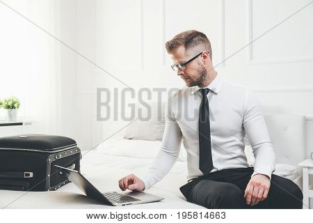 Businessman Working From A Hotel Room With His Laptop