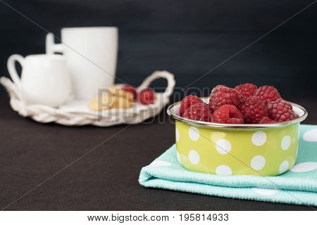 Green Bowl With Polka Dot Full With Raspberries. Cup Of Coffee, Cookies A Jug Of Milk On A Straw Tra