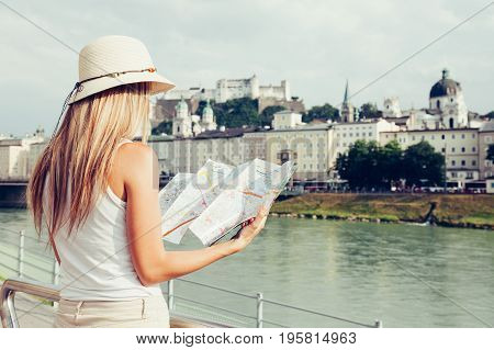 Female Tourist On Vacation In Salzburg Austria Holding A Local Map