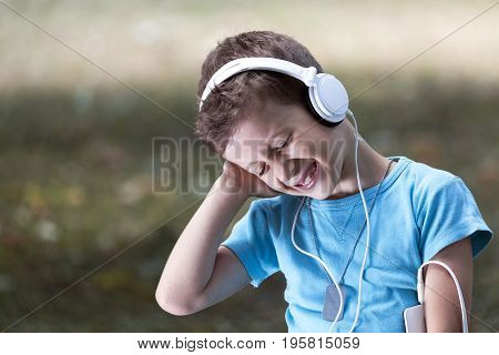 Portrait Of A Sweet Little Boy Listening To Music