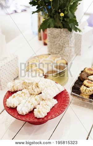 Candy bar Table with sweets candies dessert. French meringue cookies in red high plateau tray. Egg white sweets biscuits and flowers on a white wooden table