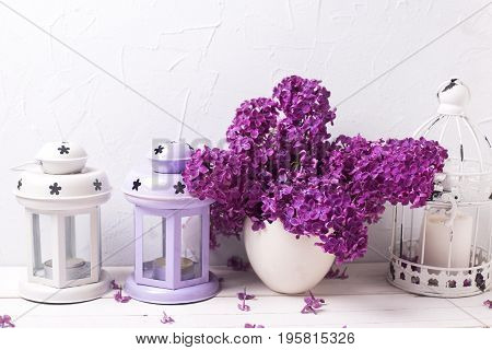 Flowers composition. Splendid lilac flowers and lanterns on white wooden background against grey textured wall. Selective focus. Shabby chic.