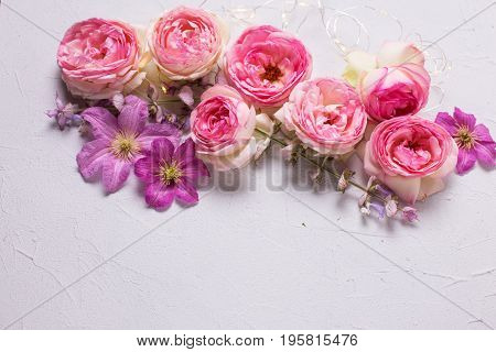 Fresh pink roses and violet summer clematis flowers on grey background. Place for text. Flat lay. Mock up.