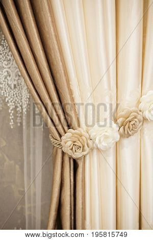 Part Of Beautifully Draped Curtain On The Window In The Room. Floral Tieback. Close Up Of Piled Curt
