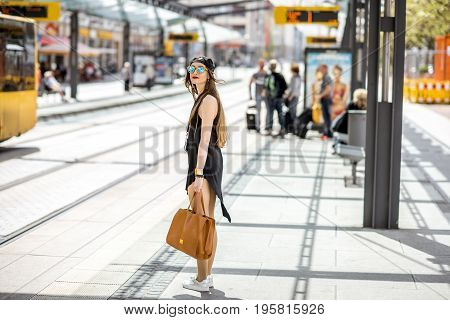 Lifestyle portrait of a stylish woman in black dress and hat walking with bag on the tram stop in the modern city