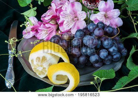 Still life in antique style with pink flowers grapes and lemon on a pewter plate